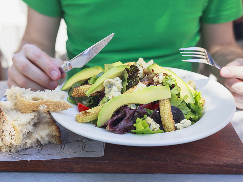 person eating plate of healthy salad