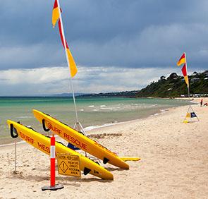thumbnail image mornington beach with safe swimming flags and kayaks