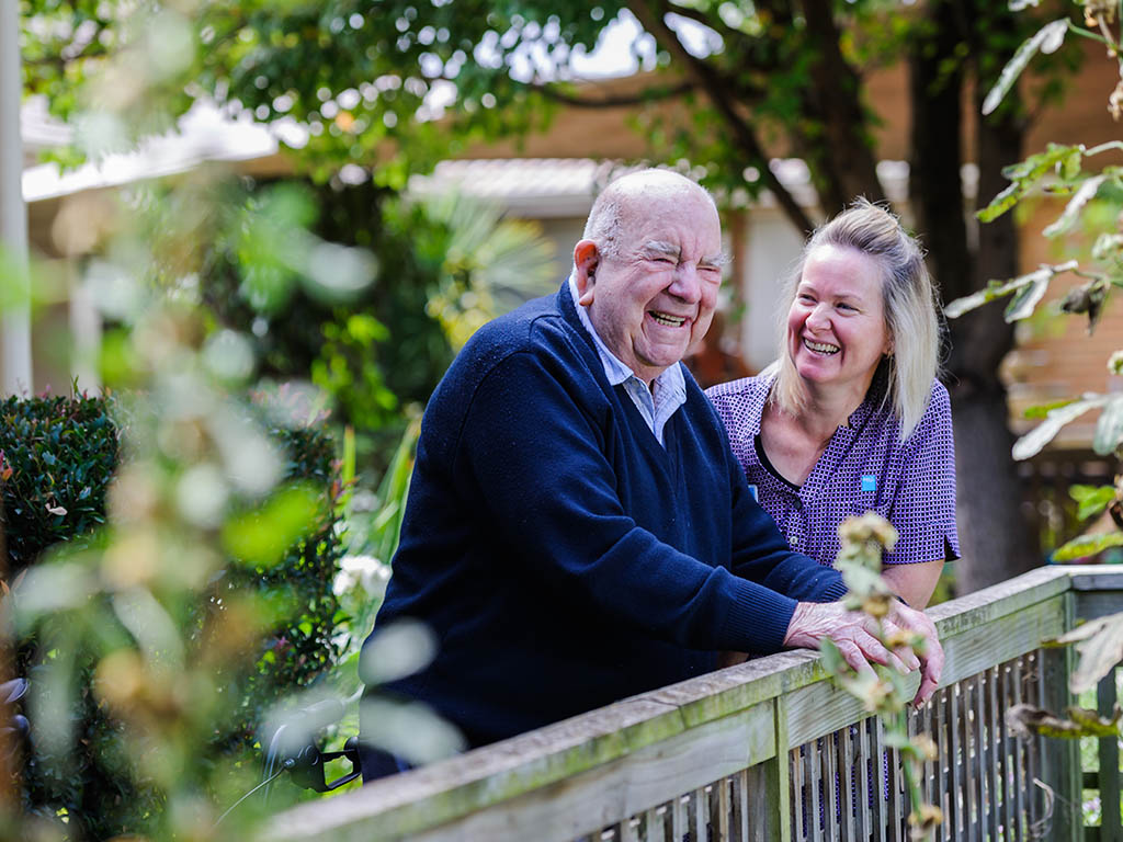 elderly man and professional carer in garden