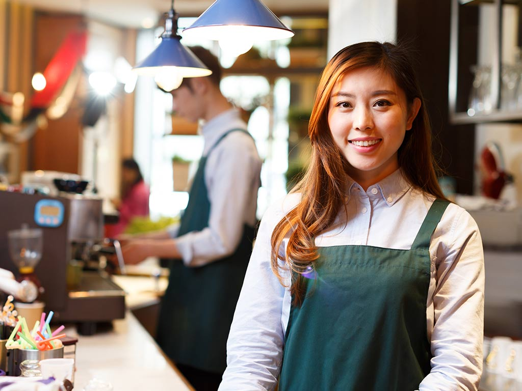 Female international student hospitality worker foreground coffee shop behind