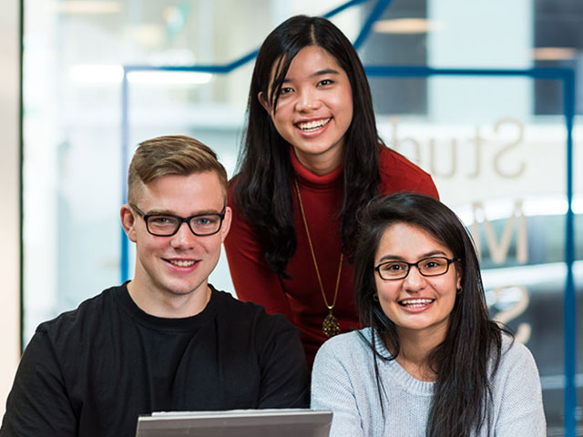 three smiling international students at a computer