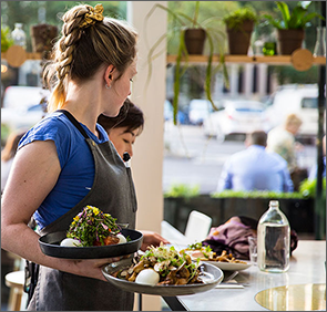 waitress holding salads in cafe